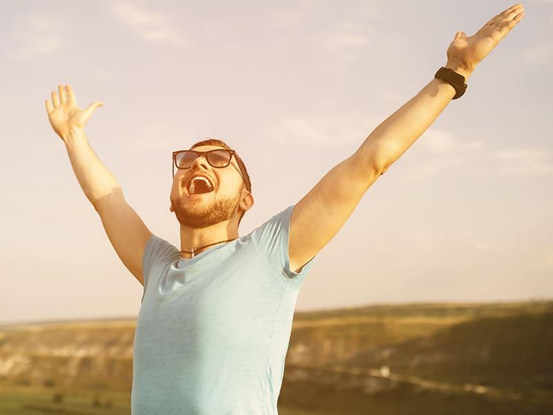 Mann freut sich in der Natur und streckt die Arme