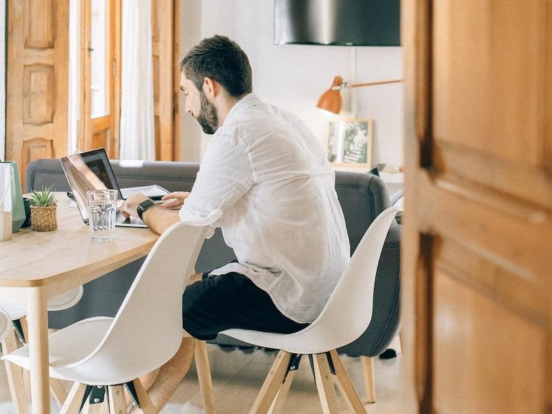 Mann sitzt am Esstisch und schaut auf seinen Laptop