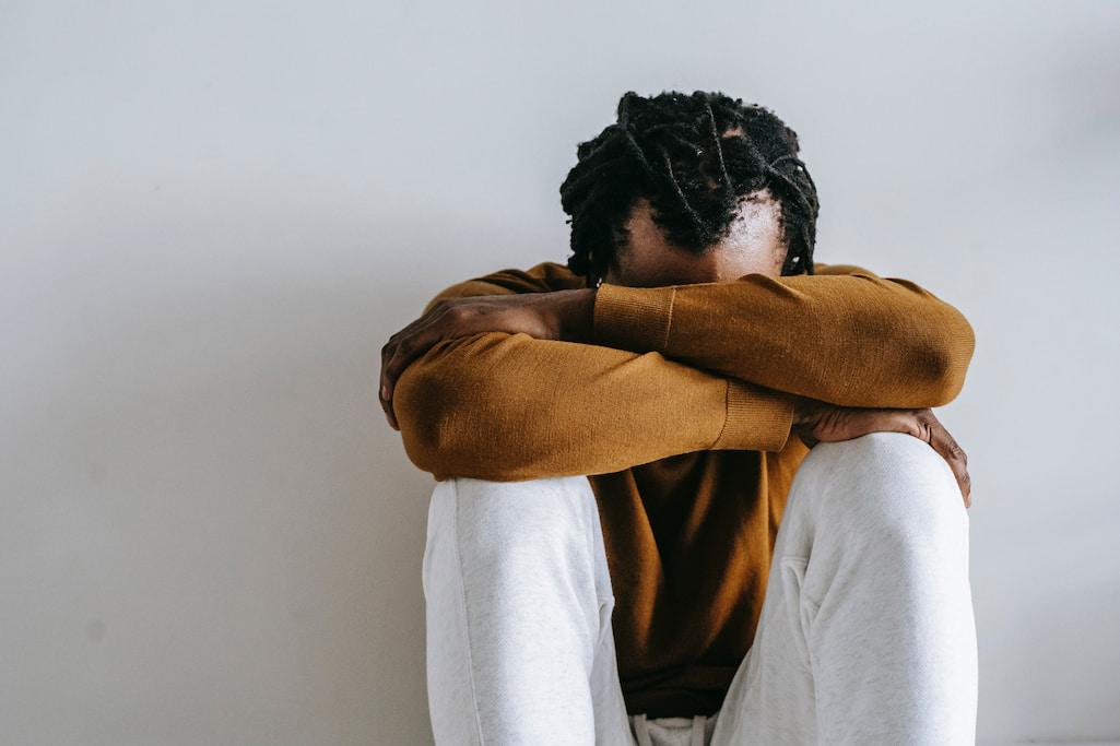 Mann sitzt mit aufgestellten Beinen deprimiert auf dem Boden, den Kopf auf die verschränkten Arme gelegt