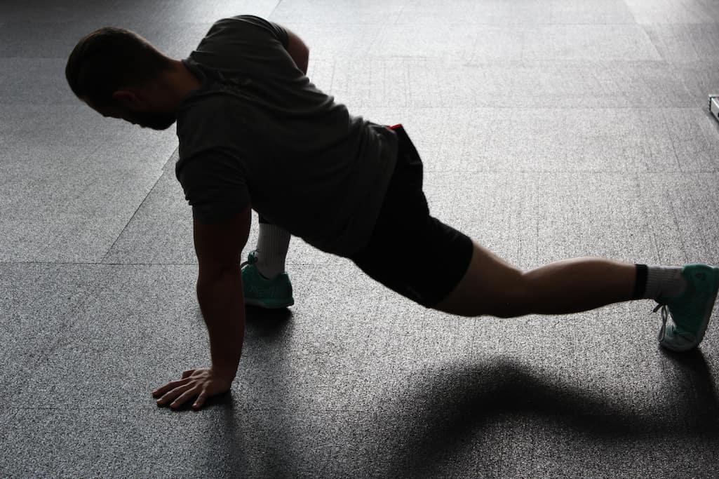 Mann in Sportkleidung mach Beckenbodentraining auf dem Boden