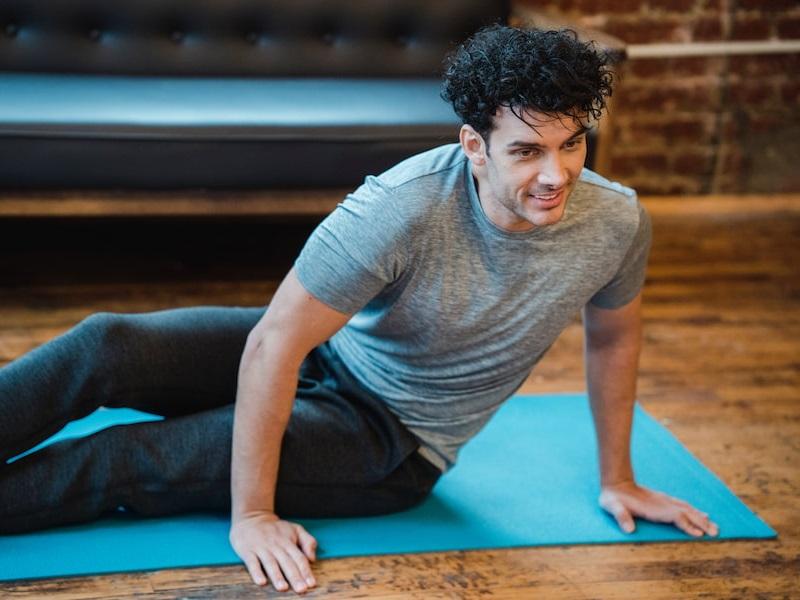 Mann in Sportkleidung sitzt seitlich auf einer blauen Yogamatte